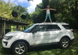 photo of girl standing on car